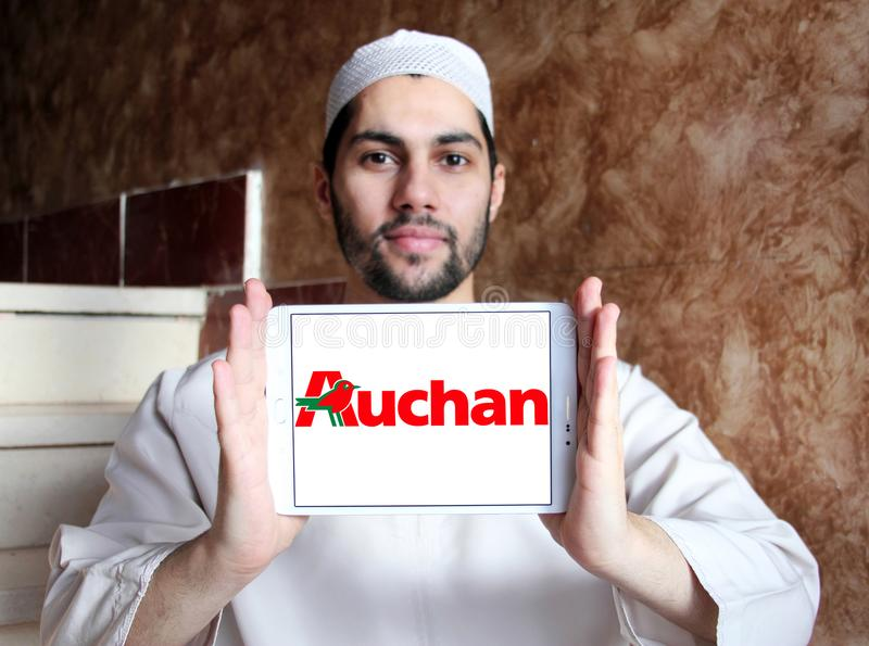 Auchan retail group logo. Logo of Auchan retailer on samsung tablet holded by arab muslim man. Auchan is a French international retail group and multinational stock images