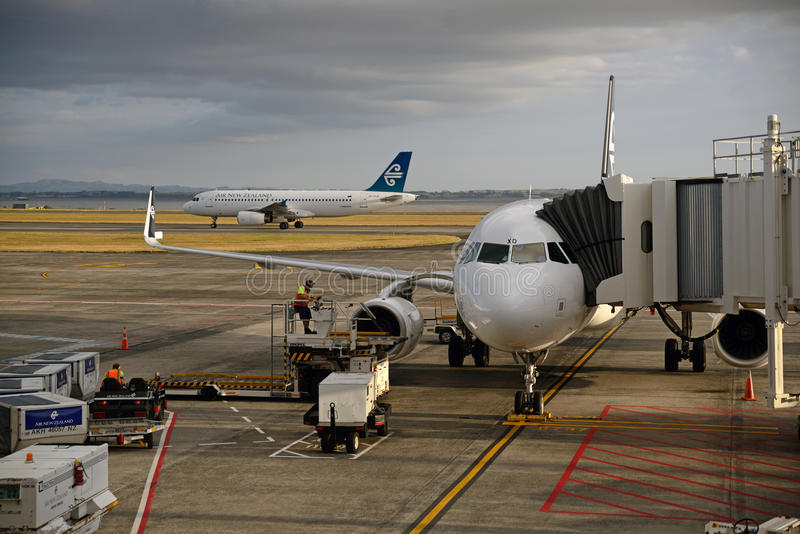 Auckland airport. AUCKLAND, NEW ZEALAND, JANUARY 23, 2015: An Air New Zealand jet lands at Auckland Airport while another takes on passengers, Northland, New royalty free stock photo