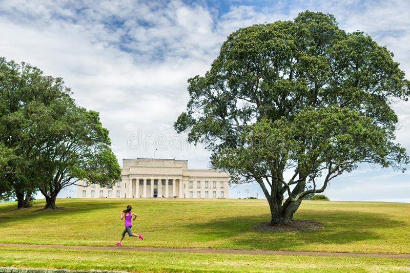 Auckland city park running jogging girl on green grass and trees at Auckland Domain park with Memorial museum . Active lifestyle royalty free stock images