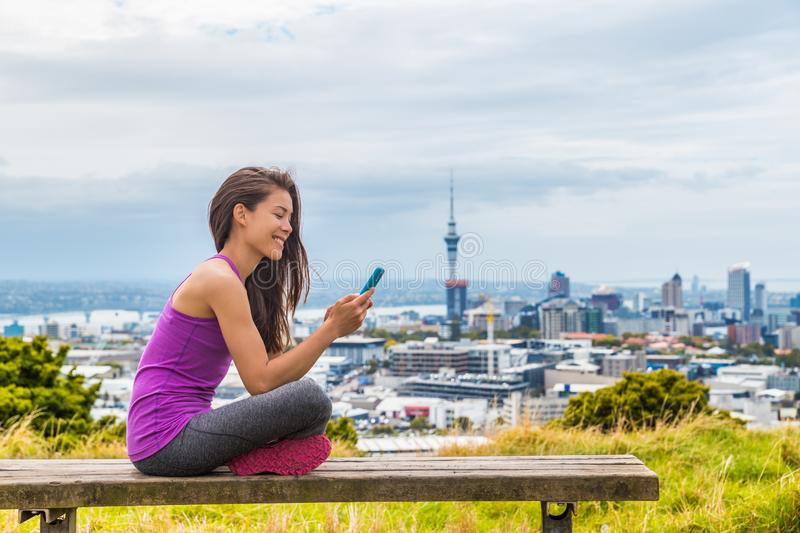 Auckland city runner girl using mobile phone app at skyline summer park. View of cityscape from Mount Eden, in North Island, New stock photo