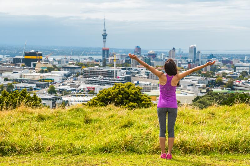 Auckland city skyline view from Mount Eden of Sky tower, New Zealand. Happy woman with arms up in freedom and happiness at top of royalty free stock photography