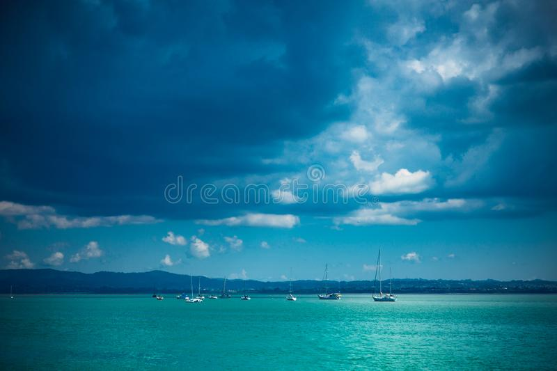 Auckland harbour with approaching rain clouds. Auckland harbour from the Auckland Harbour bridge area looking towards the west. Rain clouds are approaching stock image