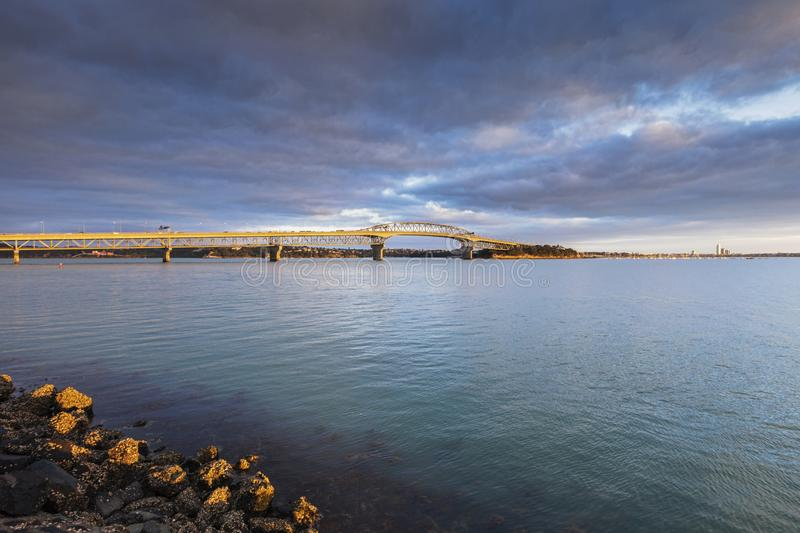 Auckland Harbour Bridge. At sunrise under a dramatic moody sky royalty free stock images