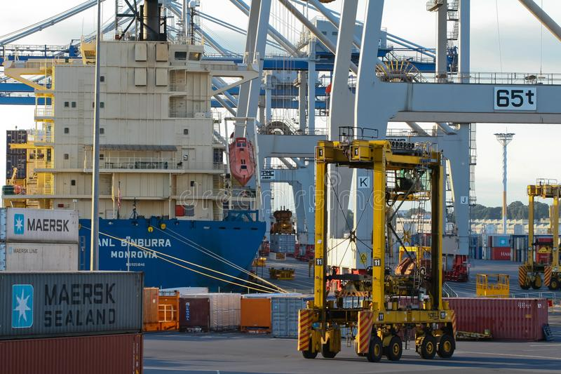 AUCKLAND, NEW ZEALAND - 17 APRIL: Vessel, straddle carriers, wheeled cranes and stack of containers at sea port. royalty free stock photography