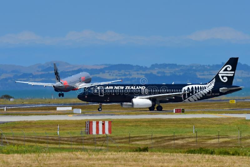 Air New Zealand Airbus A320 in special All Blacks livery taxiing as rival Jetstar Airbus A320 lands at Auckland International Airp. AUCKLAND, NEW ZEALAND stock photo