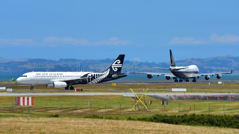 Air New Zealand Airbus A320 taxiing while Singapore Airlines Boeing 747-400 freighter takes off at Auckland International Airport. AUCKLAND, NEW ZEALAND royalty free stock photo