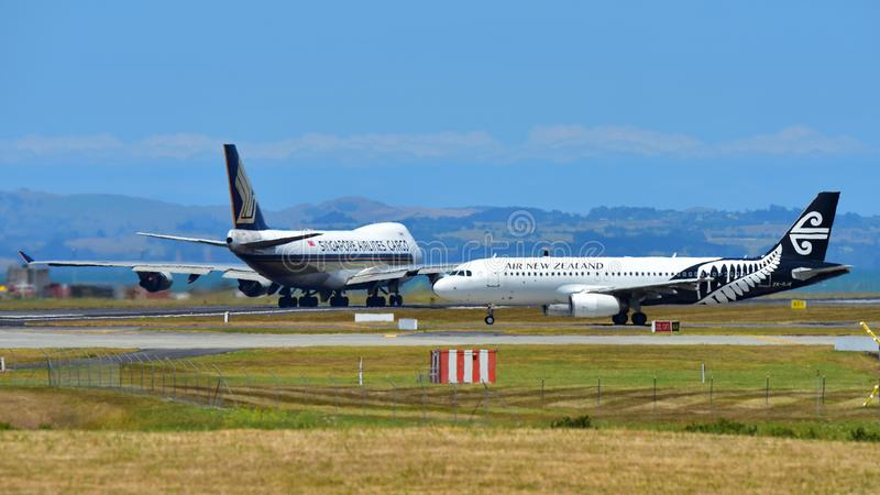 Air New Zealand Airbus A320 taxiing while Singapore Airlines Boeing 747-400 freighter takes off at Auckland International Airport. AUCKLAND, NEW ZEALAND stock images