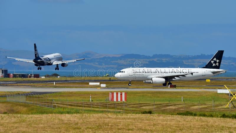 Air New Zealand A320 in Star Alliance livery taxis as another sister jet lands at Auckland International Airport. AUCKLAND, NEW ZEALAND - DECEMBER 17: Air New royalty free stock images