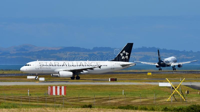Air New Zealand A320 in Star Alliance livery taxis as another sister jet lands at Auckland International Airport. AUCKLAND, NEW ZEALAND - DECEMBER 17: Air New stock photos