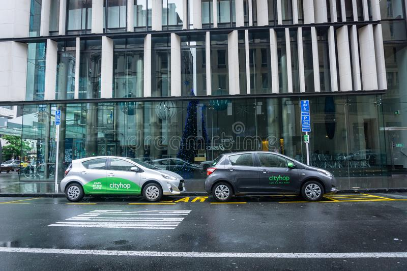 Two ride sharing cars parked in Auckland city street. AUCKLAND NEW ZEALAND - DECEMBER 23 2018; Two ride sharing cars parked in Auckland city street on light and stock photography