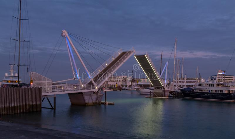 Auckland, New Zealand, November, 26, 2014; A sunset view of a swing bridge opening in the Wynard Quarter, Auckland stock photography