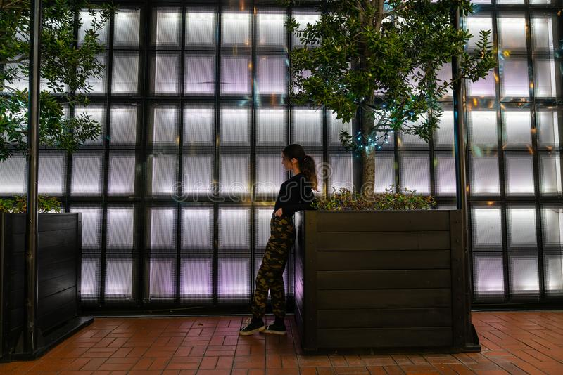 Auckland`s Britomart area. AUCKLAND, NEW ZEALAND - SEPTEMBER 14 2018; Girl leaning looking pensive on planter in front of panneled back-lit wall in Auckland`s stock photography