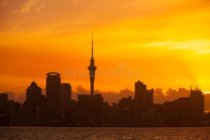 Auckland New Zealand Skyline. Auckland, New Zealand skyline at sunset with vibrant orange sky and silhouetted buildings stock image