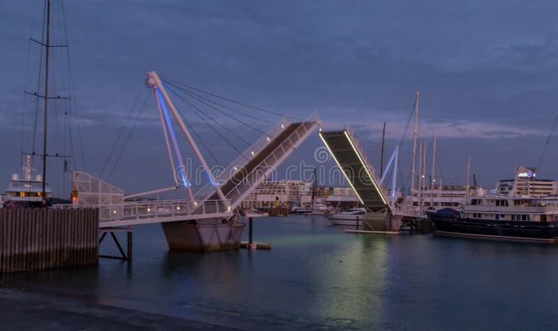 Auckland, Nova Zelândia, novembro, 26, 2014; Uma ideia do por do sol de uma abertura da ponte de balanço no quarto de Wynard, Auc fotografia de stock