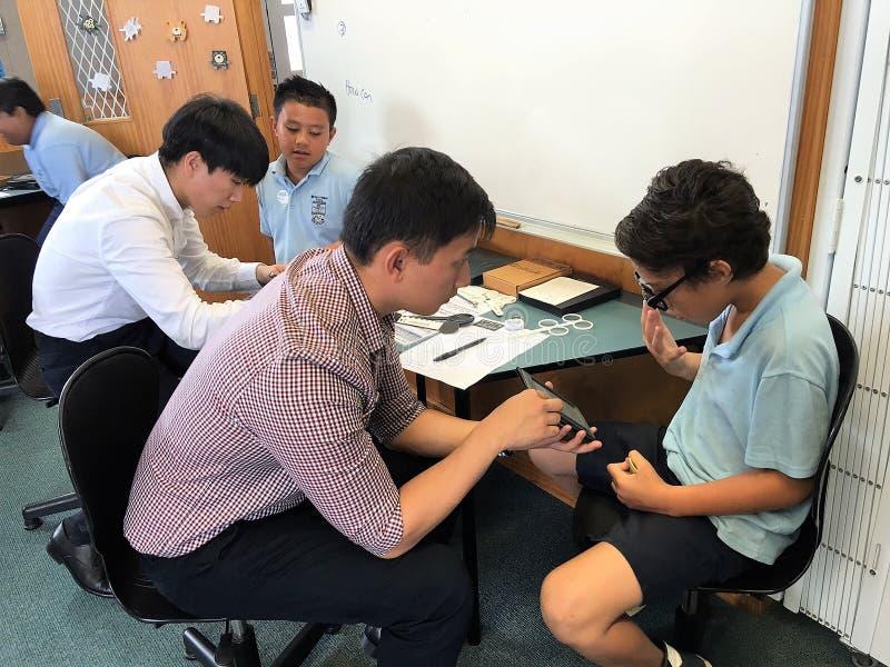 Auckland Nueva Zelanda 11mo de los ópticos de marzo de 2016 que comprueban la vista del ojo de alumnos en escuela primaria imagen de archivo