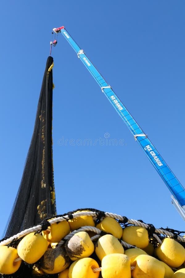 AUCKLAND NYA ZEELAND - JUNI 14, 2012: Hissa lyfter upp stort industriellt fisknät över himmelbakgrund royaltyfri foto