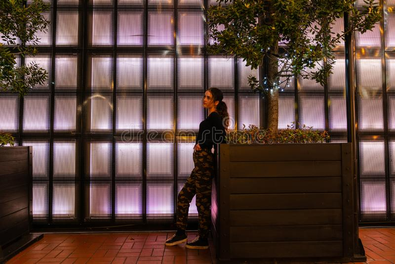 Auckland`s Britomart area. AUCKLAND, NEW ZEALAND - SEPTEMBER 14 2018; Girl leaning looking pensive on planter in front of panneled back-lit wall in Auckland`s royalty free stock images
