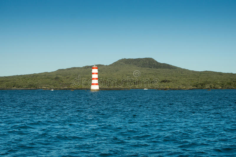 Aucklands Iconic Rangitoto Island. The recently active volcano island of Rangitoto under blue sky in Auckland New Zealand. A nature reserve iconic Rangitoto sits royalty free stock photo