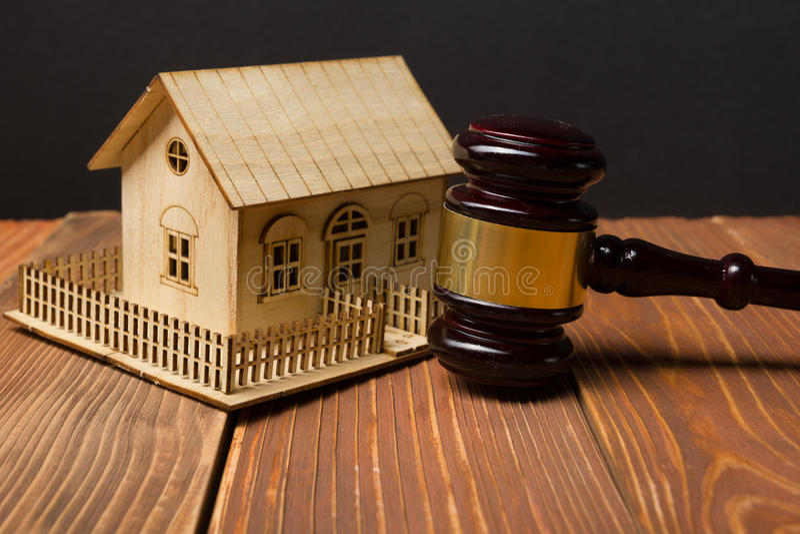 auction gesetz Miniaturhaus auf Holztisch und Gerichts-Hammer lizenzfreies stockfoto