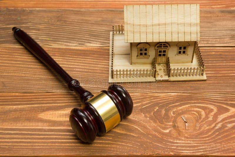 auction gesetz Miniaturhaus auf Holztisch und Gerichts-Hammer stockfotografie