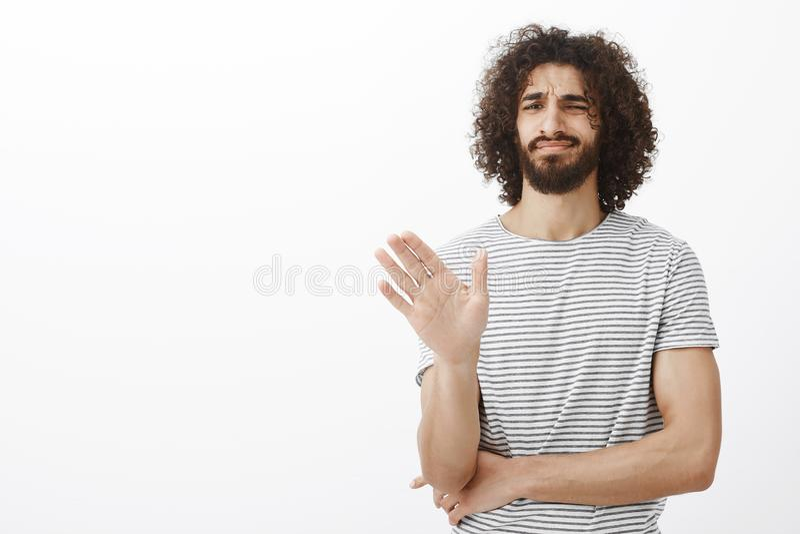 Aucun mercis, je passe Mâle aux cheveux bouclés beau indifférent contrarié dans le T-shirt rayé élégant, la paume de ondulation d photos stock