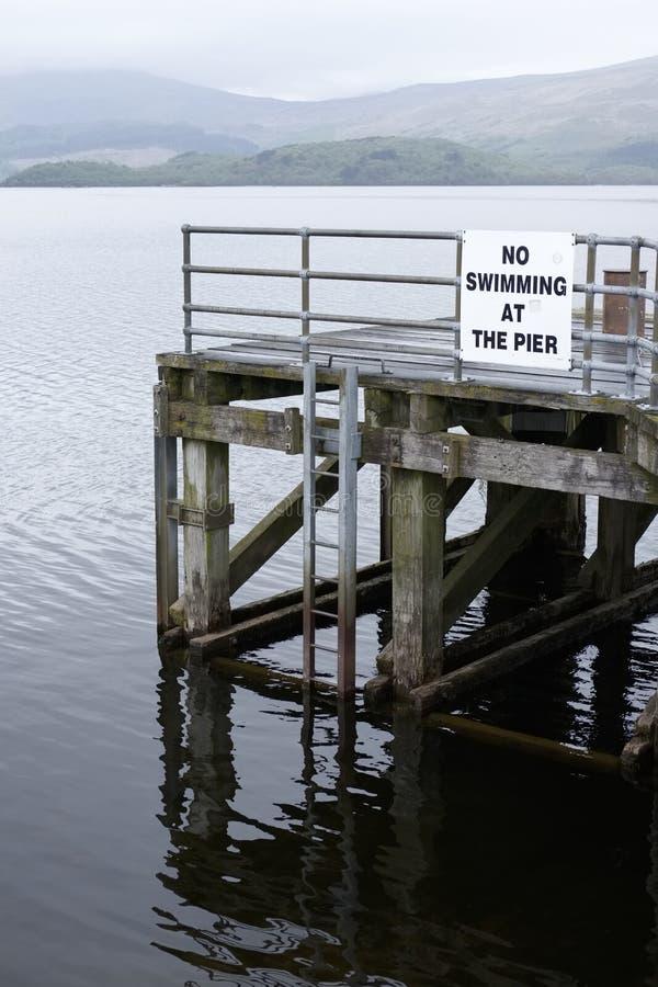 Aucune natation au danger de panneau d'avertissement de Loch Lomond Luss d'eau profonde de jetée de pilier de la mort image libre de droits