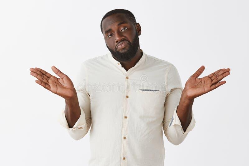 Aucuns regrets Portrait du collègue négligent et indifférent d'Afro-américain dans la chemise blanche gesticulant avec les mains  images stock