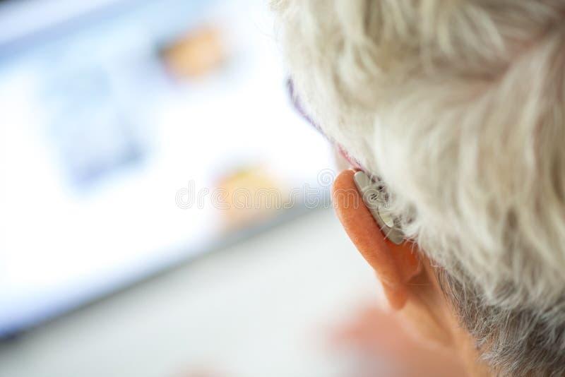 Audífono que lleva mayor en sus oídos en frente un ordenador portátil foto de archivo