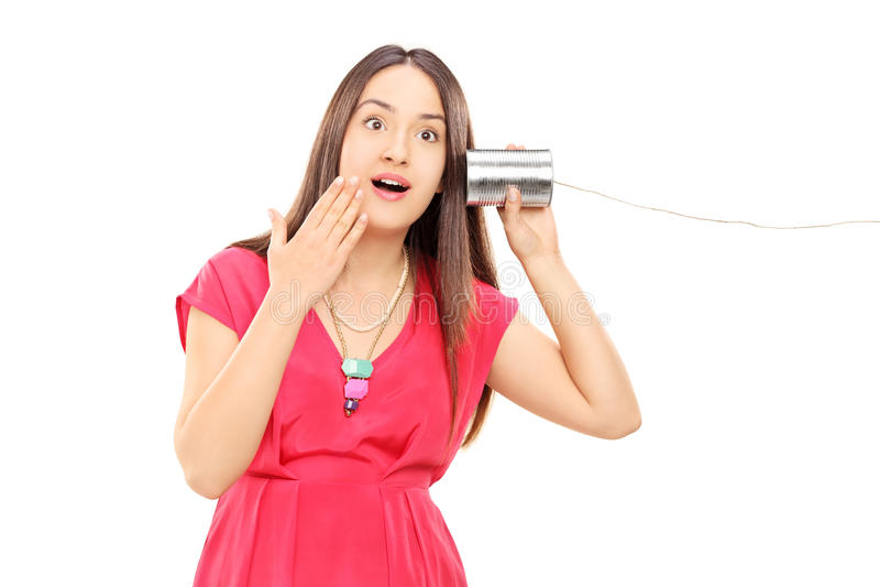 Audição da mulher algo através de um telefone da lata de lata imagem de stock
