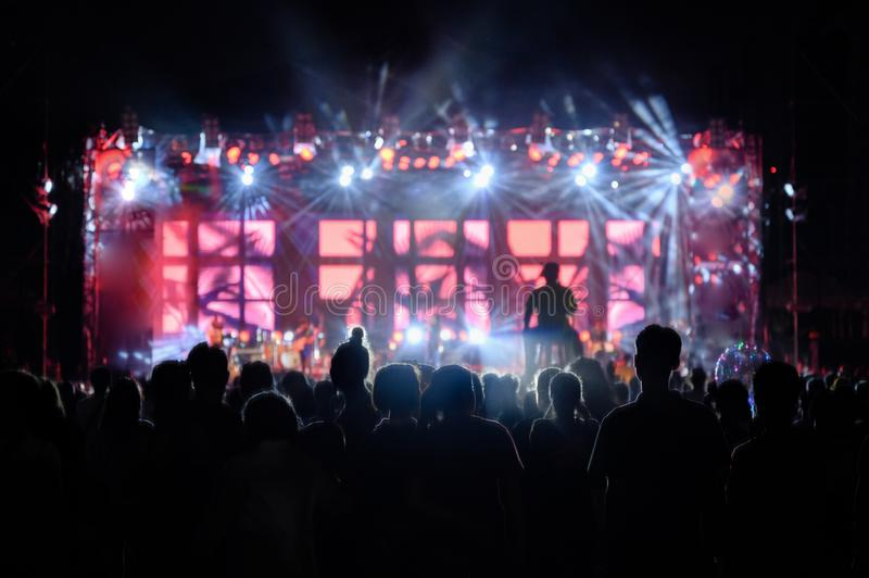 A audiência da juventude da silhueta está olhando o concerto da noite fotos de stock