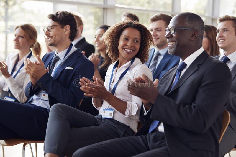 Audiência de sorriso que aplaude em um seminário do negócio fotos de stock royalty free
