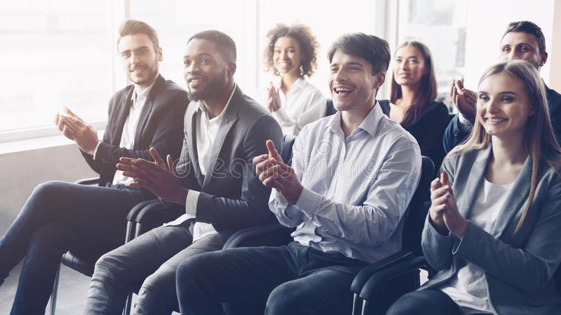 Audiência do negócio que aplaude ao orador na conferência imagem de stock