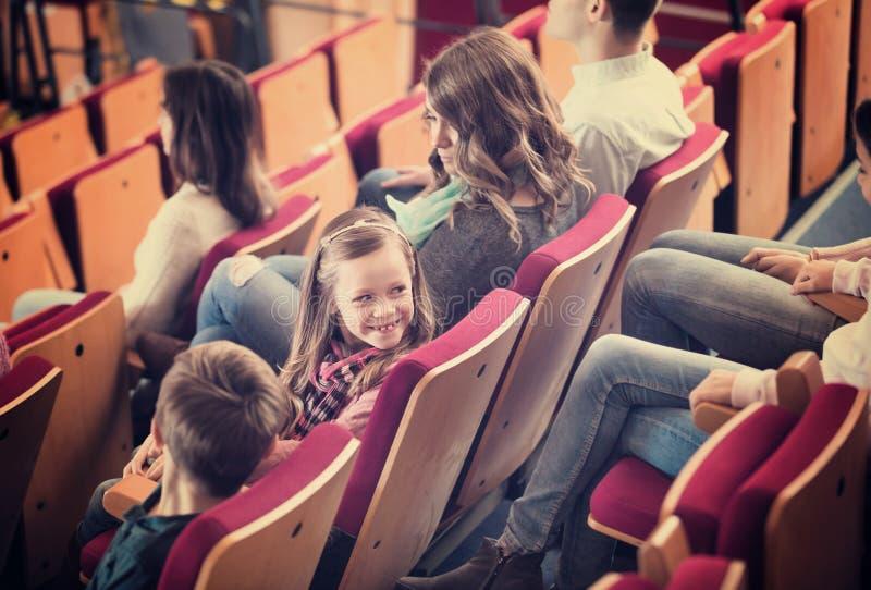 Audiência entusiástica que come a pipoca e que olha um filme foto de stock