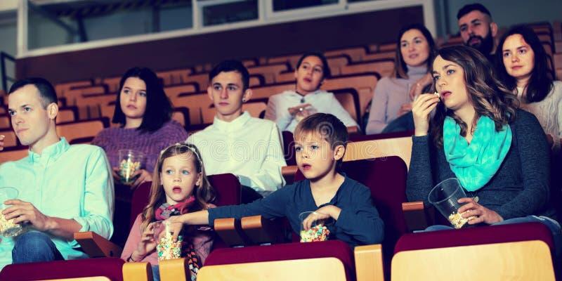 Audiência entusiástica que come a pipoca e que olha um filme fotos de stock royalty free