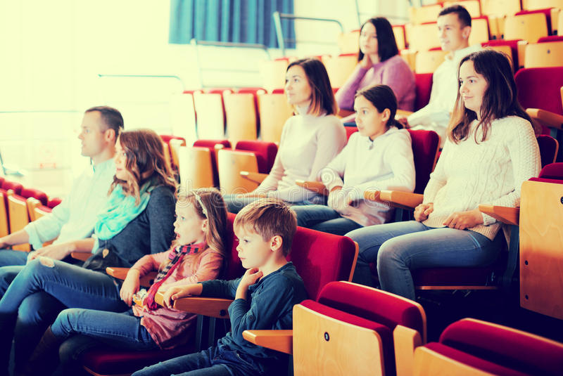 Audiência entusiástica que come a pipoca e que olha um filme foto de stock royalty free