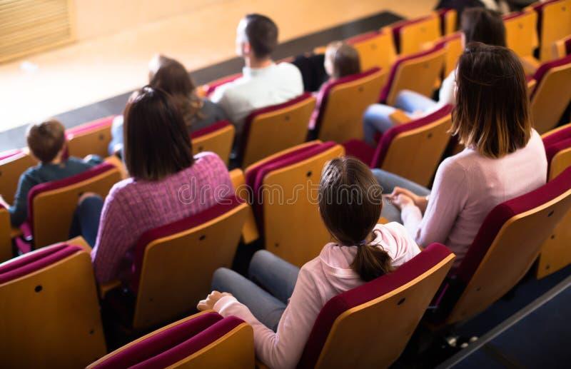 Audiência entusiástica que come a pipoca e que olha um filme imagem de stock royalty free