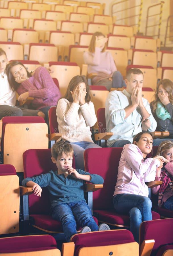 Audiência entusiástica que come a pipoca e que olha um filme fotografia de stock