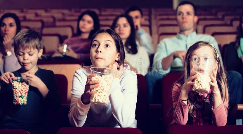 Audiência entusiástica que come a pipoca e que olha um filme fotos de stock