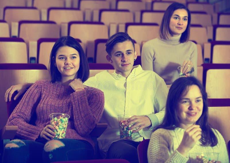 Audiência entusiástica que come a pipoca e que olha um filme imagem de stock