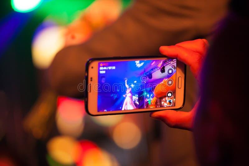 Audiência que captura o desempenho de um artista, quando na fase, usando sua câmera do telefone fotografia de stock