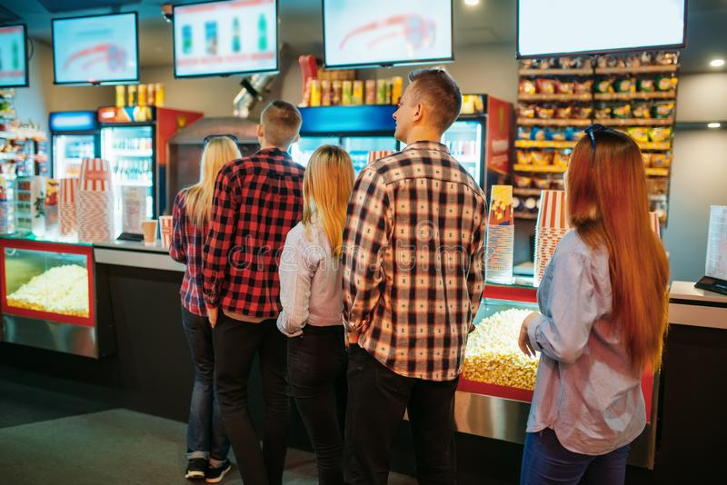 Audience choosing food in cinema bar. Before the showtime, back view. Male and female youth in movie theater royalty free stock photography