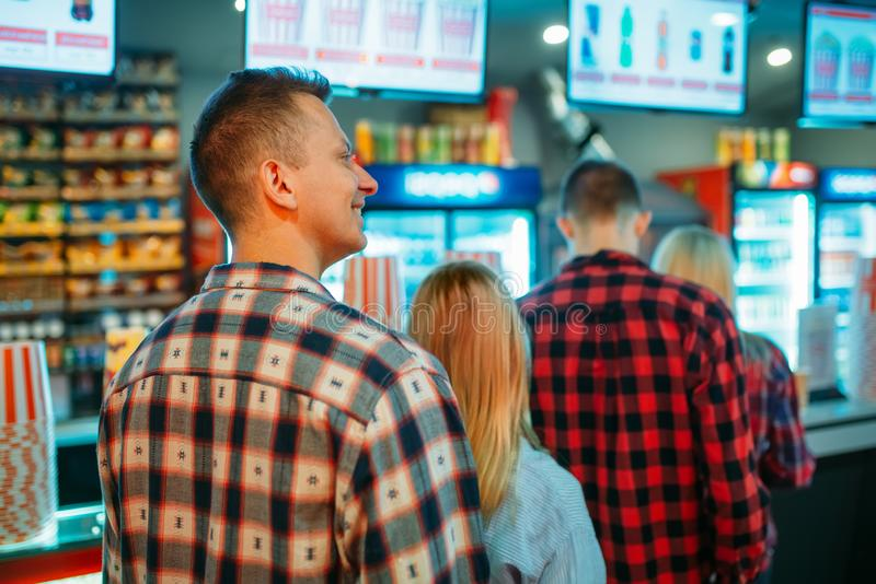 Audience choosing food in cinema bar. Before the showtime, back view. Male and female youth in movie theater stock photography