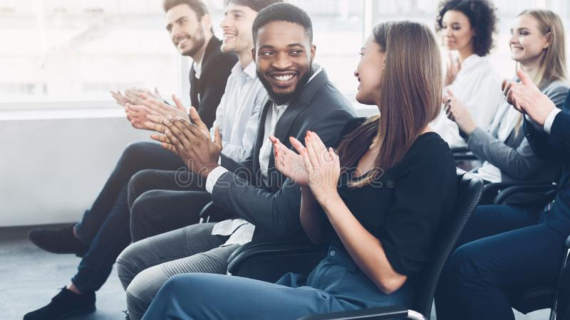 Audience clapping hands at seminar, looking at each other royalty free stock photos