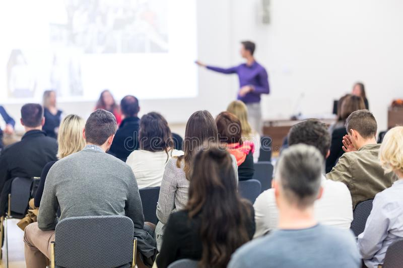 Audience in lecture hall participating at business conference. stock photos