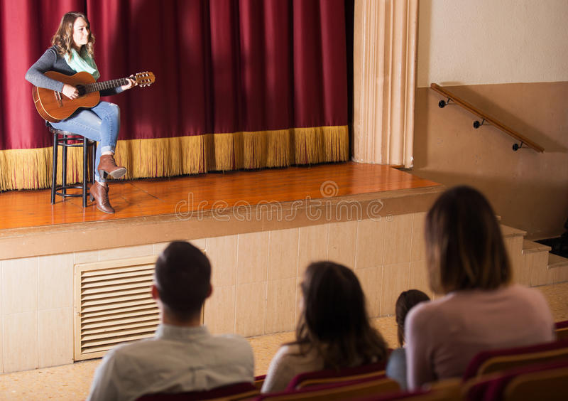 Audience listening to guitar concert. Adult audience listening to guitar concert in concert hall indoors royalty free stock image
