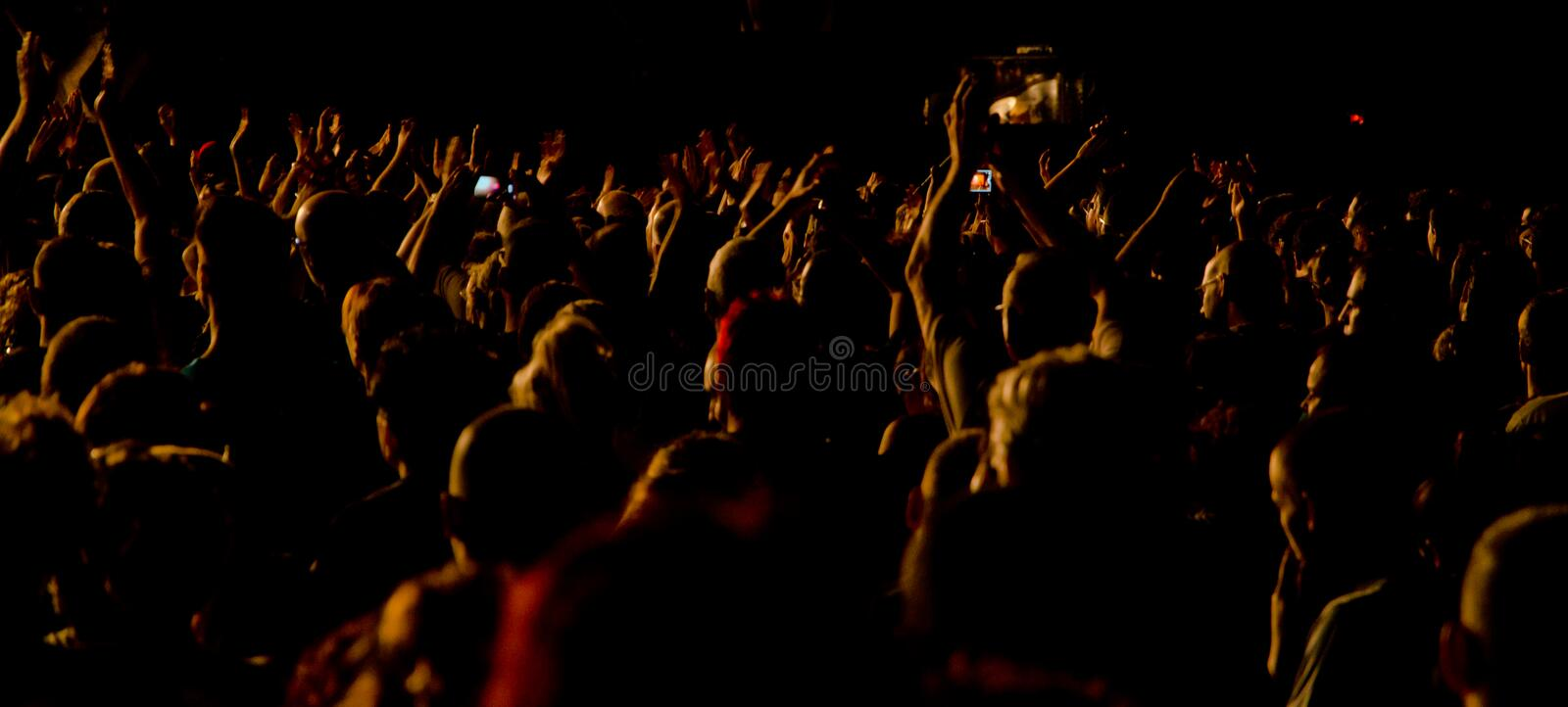 Audience at live concert. Large audience at live rock concert cheering with bright light at stage area royalty free stock image