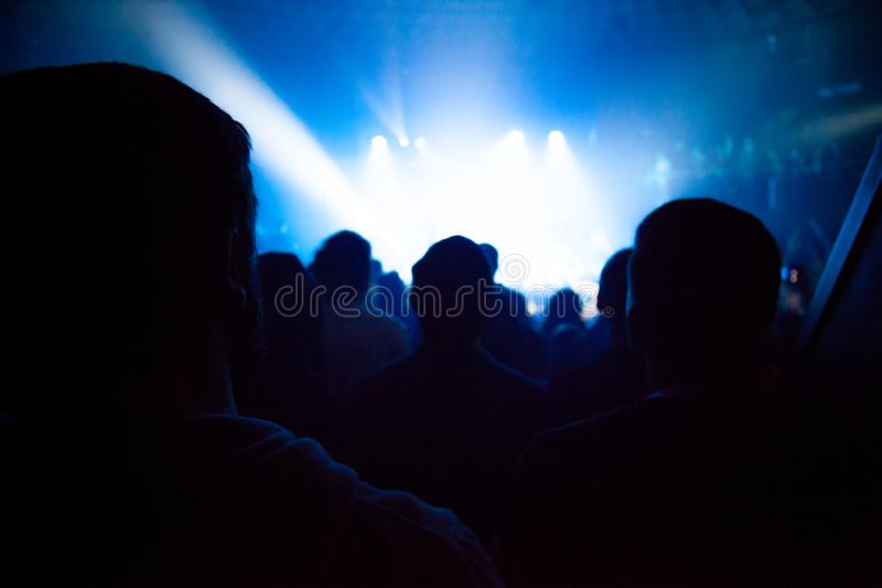Audience silhouettes crowd in large concert hall watching rock show. stock photos