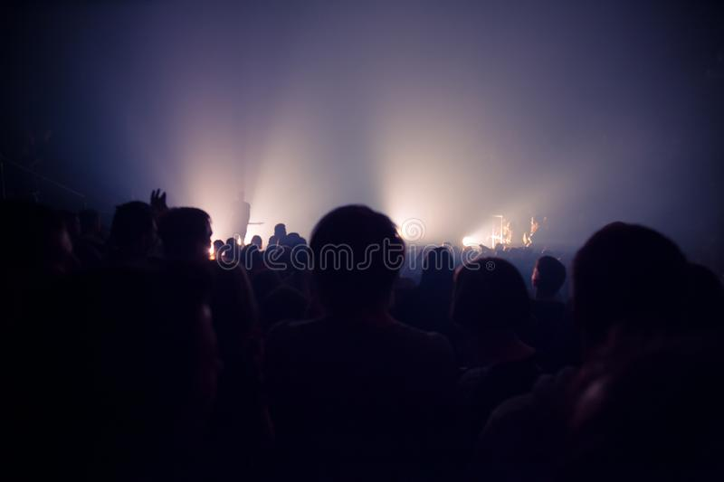Audience silhouettes crowd in large concert hall watching rock show. stock photography