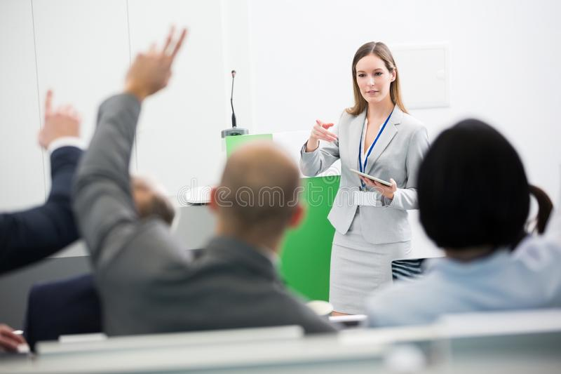 Audiencia de Asking Questions To de la empresaria mientras que sostiene la tableta de Digitaces imagen de archivo libre de regalías