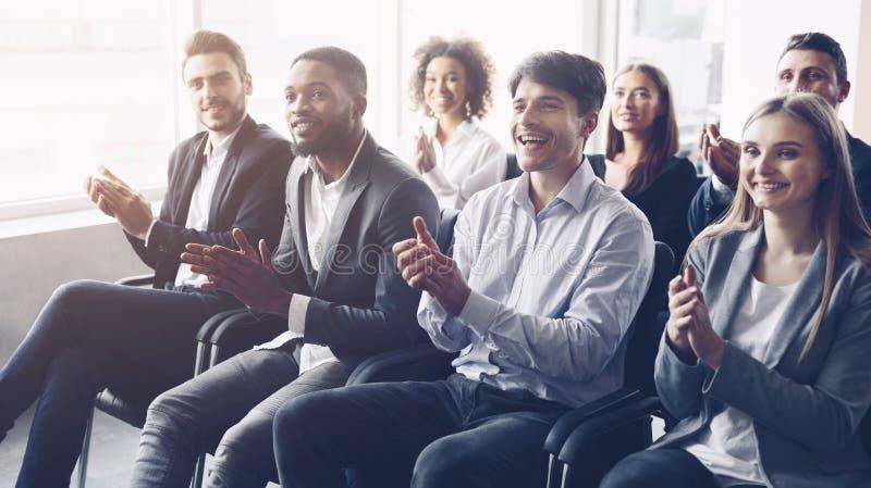 Audiencia del negocio que aplaude al altavoz en la conferencia imagen de archivo